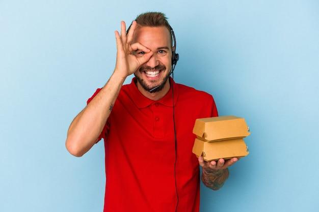 Jeune livreur caucasien avec des tatouages tenant des hamburgers isolés sur fond bleu excité en gardant le geste ok sur les yeux.