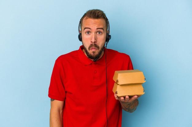 Jeune livreur caucasien avec des tatouages tenant des hamburgers isolés sur fond bleu hausse les épaules et ouvre les yeux confus.