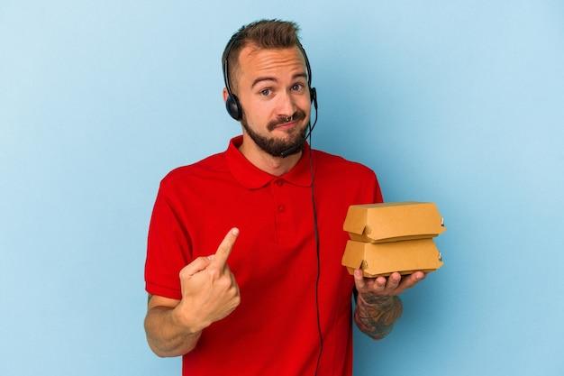 Jeune livreur caucasien avec des tatouages tenant des hamburgers isolés sur fond bleu pointant du doigt vers vous comme s'il vous invitait à vous rapprocher.