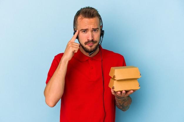 Jeune livreur caucasien avec des tatouages tenant des hamburgers isolés sur fond bleu pointant le temple avec le doigt, pensant, concentré sur une tâche.