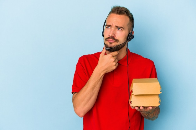 Jeune livreur caucasien avec des tatouages tenant des hamburgers isolés sur fond bleu regardant de côté avec une expression douteuse et sceptique.