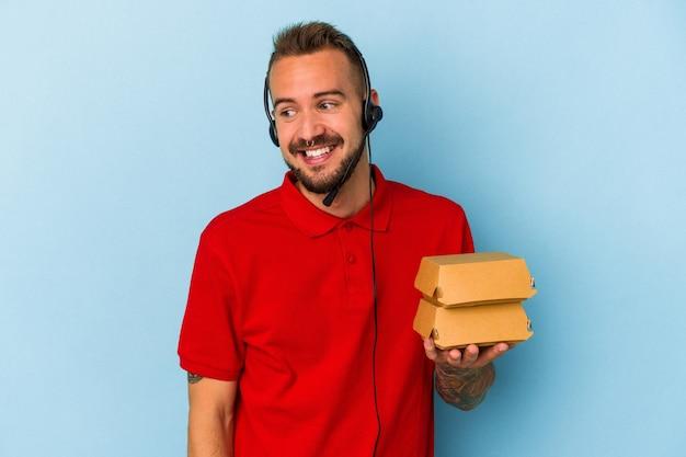 Jeune livreur caucasien avec des tatouages tenant des hamburgers isolés sur fond bleu regarde de côté souriant, joyeux et agréable.