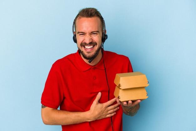 Jeune livreur caucasien avec des tatouages tenant des hamburgers isolés sur fond bleu en riant et en s'amusant.