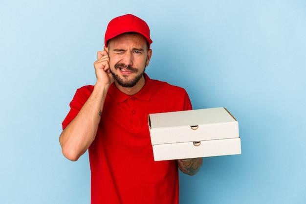 Jeune livreur caucasien avec des tatouages tenant des pizzas isolées sur fond bleu couvrant les oreilles avec les mains.