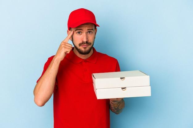 Jeune livreur caucasien avec des tatouages tenant des pizzas isolées sur fond bleu pointant le temple avec le doigt, pensant, concentré sur une tâche.