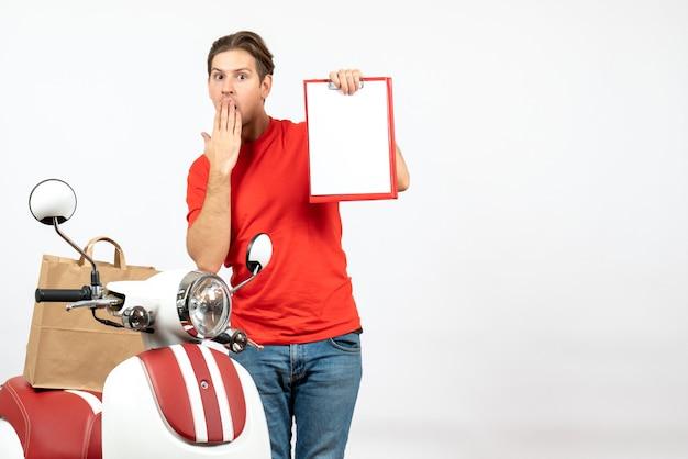 Jeune livreur choqué en uniforme rouge debout près de scooter montrant un document sur un mur blanc