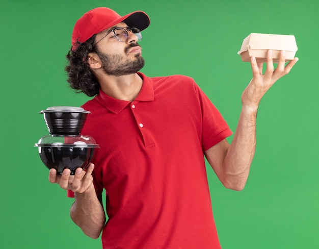 Jeune livreur confus en uniforme rouge et casquette portant des lunettes tenant un emballage de nourriture en papier et des contenants de nourriture regardant un emballage de nourriture isolé sur un mur vert
