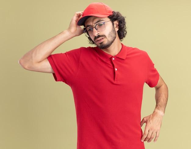 Jeune livreur confus en uniforme rouge et casquette portant des lunettes touchant la tête regardant vers le bas isolé sur un mur vert olive