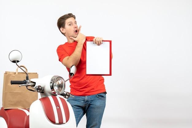 Jeune livreur confus en uniforme rouge debout près de scooter montrant un document sur un mur blanc