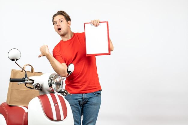 Jeune livreur confus en uniforme rouge debout près de scooter montrant le document de pointage sac en papier sur mur blanc