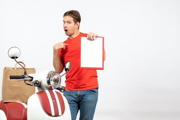 Jeune livreur confus en uniforme rouge debout près de scooter montrant le document se pointant sur le mur blanc