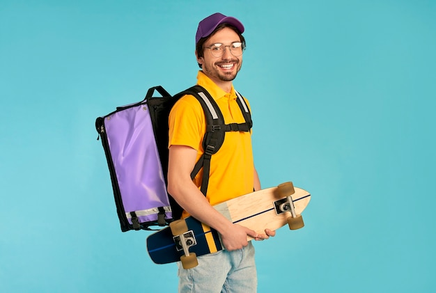 Jeune livreur de courrier en uniforme avec sac à dos thermo et skate isolé. livraison express à domicile rapide. commande en ligne.