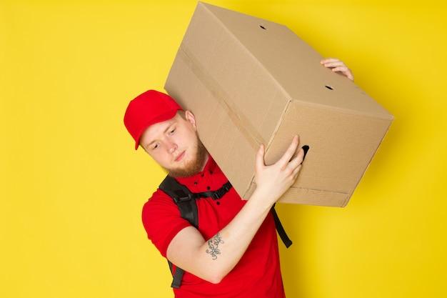 Jeune, livreur, dans, polo rouge, casquette rouge, jean blanc, tenue, a, boîte, sur, jaune