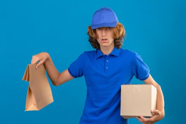 Jeune livreur douteux portant un polo bleu et une casquette tenant une boîte en carton et un paquet de papier regardant la caméra avec des doutes debout sur fond bleu isolé
