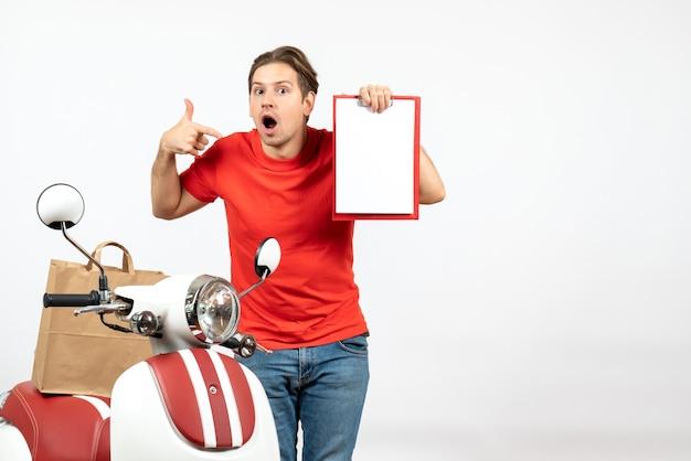 Jeune livreur émotionnel et confus en uniforme rouge debout près de scooter montrant un document pointant quelque chose sur le mur blanc