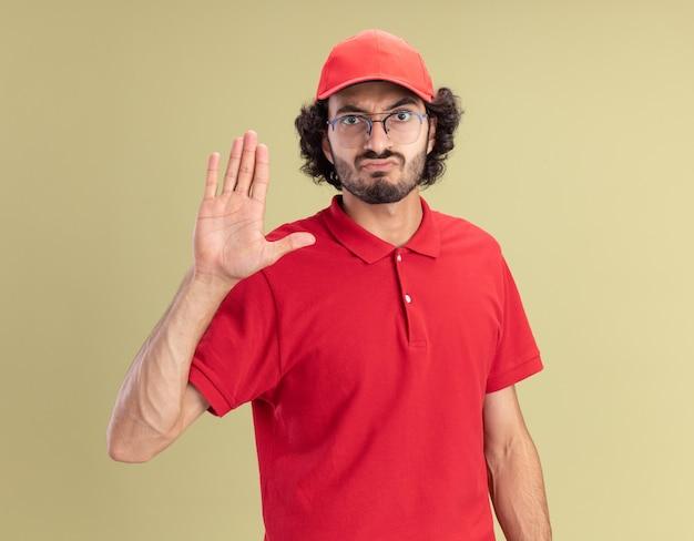 Jeune livreur fronçant les sourcils en uniforme rouge et casquette portant des lunettes regardant devant faisant un geste d'arrêt isolé sur un mur vert olive