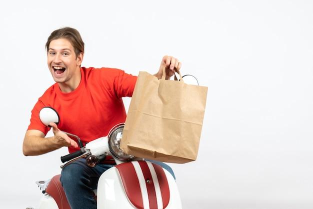 Jeune livreur heureux en uniforme rouge assis sur un scooter tenant un sac en papier sur un mur blanc