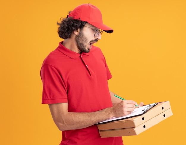 Jeune livreur impressionné en uniforme rouge et casquette portant des lunettes debout en vue de profil tenant des colis de pizza écrivant sur un presse-papiers avec un crayon isolé sur un mur orange