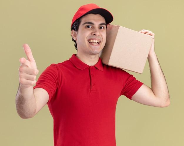 Jeune livreur impressionné en uniforme rouge et casquette tenant une boîte à cartes sur l'épaule regardant et pointant vers l'avant isolé sur un mur vert olive