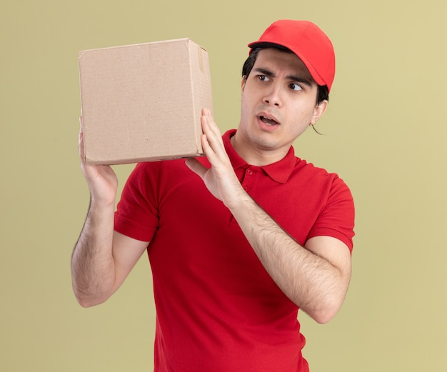 Jeune livreur impressionné en uniforme rouge et casquette tenant et regardant la boîte à cartes isolée sur un mur vert olive