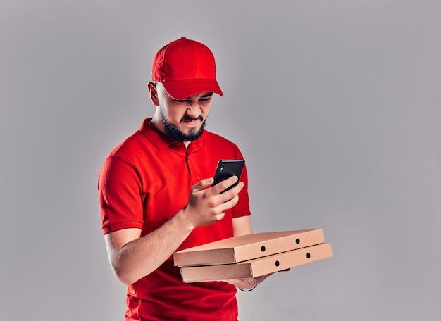 Jeune livreur mécontent en colère barbu en t-shirt rouge et casquette avec boîtes à pizza et smartphone isolé sur fond gris. livraison rapide à domicile.