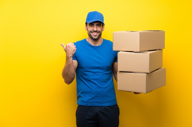 Jeune livreur sur un mur jaune isolé pointant sur le côté pour présenter un produit
