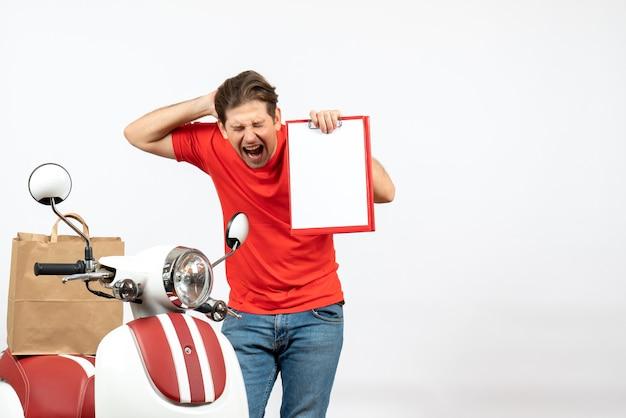 Jeune livreur nerveux émotionnel en uniforme rouge debout près de scooter montrant un document sur un mur blanc