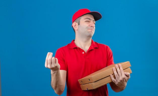 Jeune livreur en polo rouge et cap tenant des boîtes de pizza faisant de délicieux geste italien avec main souriant sur mur bleu isolé