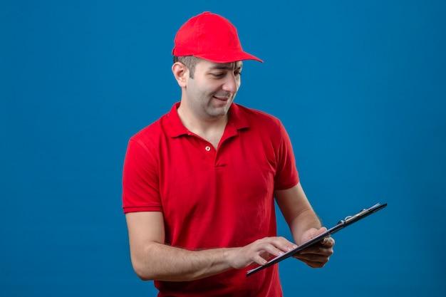 Jeune livreur en polo rouge et capuchon regardant le presse-papiers dans les mains avec sourire sur le visage debout sur fond bleu isolé