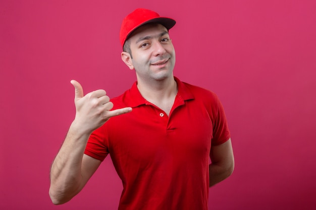 Jeune livreur en polo rouge et casquette faisant appelez-moi geste à la confiance souriant joyeusement sur fond rose isolé