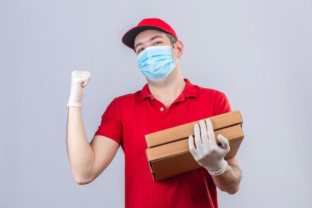 Jeune livreur en polo rouge et casquette en masque médical tenant des boîtes de pizza pointant vers l'arrière derrière avec la main et le pouce vers le haut à la confiance sur mur blanc isolé