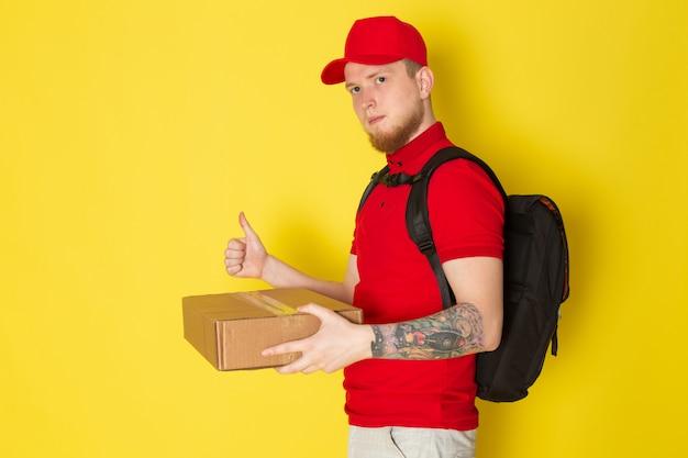Jeune livreur en polo rouge casquette rouge jeans blancs et sac à dos noir tenant une boîte sur jaune