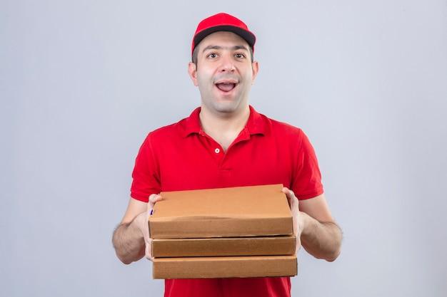 Jeune livreur en polo rouge et casquette tenant des boîtes à pizza souriant joyeusement debout sur un mur blanc isolé