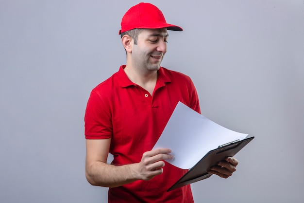 Jeune livreur en polo rouge et casquette tenant le presse-papiers à la recherche de blancs en souriant confiant debout sur mur blanc isolé