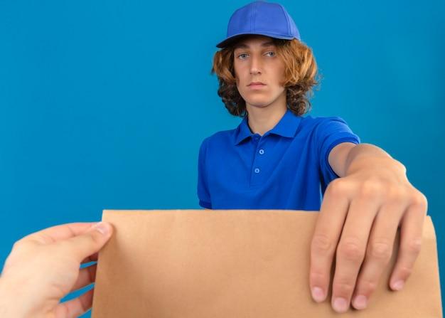 Jeune livreur portant un polo bleu et une casquette donnant un paquet de papier à un client avec un visage sérieux sur fond bleu isolé
