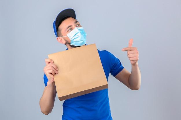 Jeune livreur portant un polo bleu et une casquette portant un masque médical de protection tenant un paquet de papier avec des plats à emporter en pointant vers ce paquet avec le doigt souriant sur backgrou blanc isolé