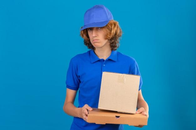 Jeune livreur portant un polo bleu et une casquette tenant une boîte en carton avec une expression triste debout sur fond bleu isolé