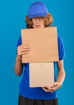 Jeune livreur portant un polo bleu et une casquette tenant une boîte en carton et un paquet de papier à la surprise debout sur fond bleu isolé