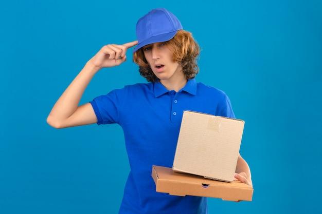 Jeune livreur portant un polo bleu et une casquette tenant des boîtes en carton pointant vers la tête avec un doigt super idée ou pensée debout sur fond bleu isolé