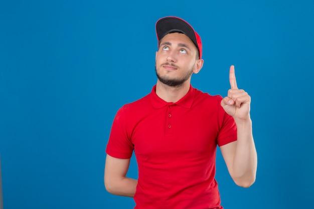Jeune livreur portant un polo rouge et une casquette à la confiance avec le doigt pointant vers le haut sur fond bleu isolé