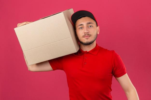 Jeune livreur portant un polo rouge et une casquette debout avec une boîte en carton sur l'épaule regardant la caméra avec un visage sérieux sur fond rose isolé