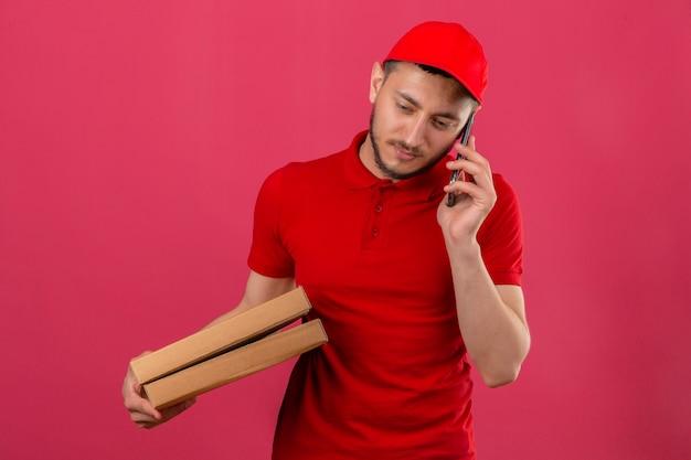 Jeune livreur portant un polo rouge et une casquette debout avec pile de boîtes de pizza parler au téléphone mobile à l'ennui et surmené sur fond rose isolé