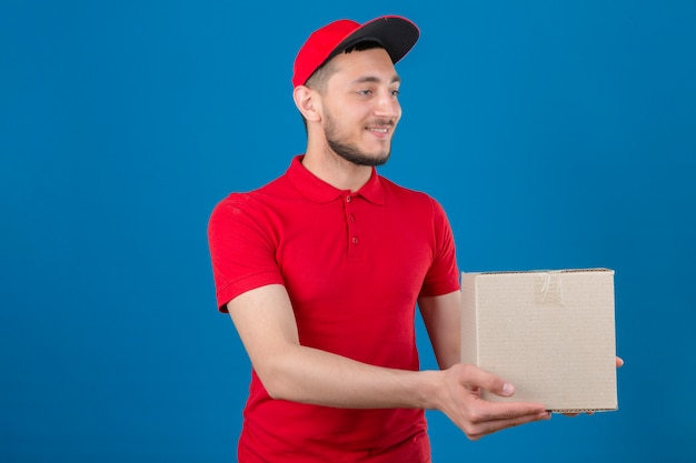Jeune livreur portant un polo rouge et une casquette donnant une boîte en carton au client avec le sourire sur le visage sur fond bleu isolé