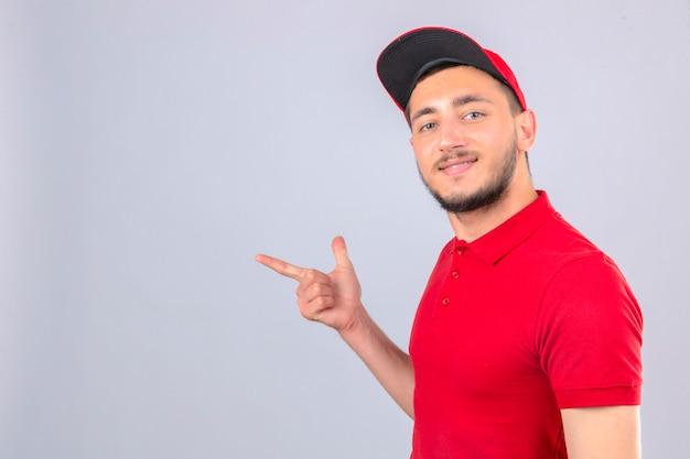 Jeune livreur portant un polo rouge et une casquette pointant le doigt vers le haut sur l'espace de copie à la recherche de sourire sur le visage sur fond blanc isolé