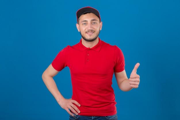Jeune livreur portant un polo rouge et une casquette regardant la caméra avec un sourire amical montrant le pouce vers le haut sur fond bleu isolé