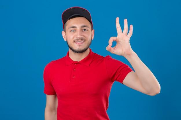Jeune livreur portant un polo rouge et une casquette regardant la caméra avec sourire faisant signe ok sur fond bleu isolé