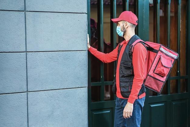 Jeune livreur avec sac à dos thermique sonnant à la porte pendant le verrouillage du coronavirus - focus sur le visage