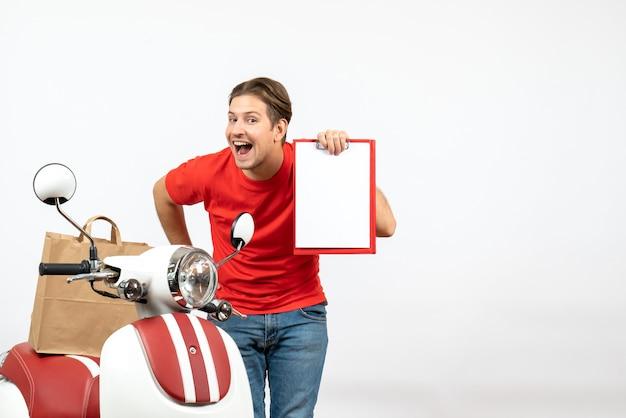 Jeune livreur souriant confiant en uniforme rouge debout près de scooter montrant un document sur un mur blanc