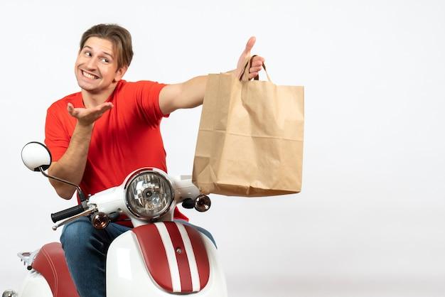 Jeune livreur souriant en uniforme rouge assis sur un scooter donnant un sac en papier à quelqu'un sur le mur jaune