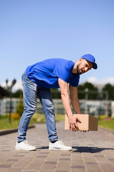 Jeune livreur transportant une boîte en carton